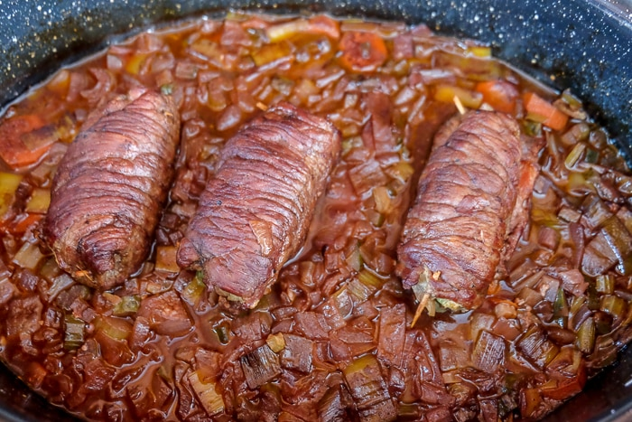 cooked rolled beef rouladen on cooked vegetables in roasting pan
