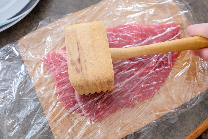 wooden hammer pounding beef between cling wrap on wooden board