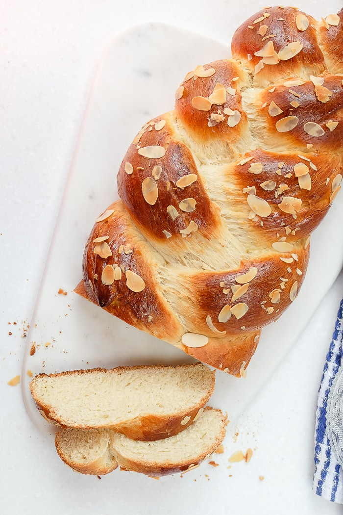 braided german sweet bread on white marble with slices cut