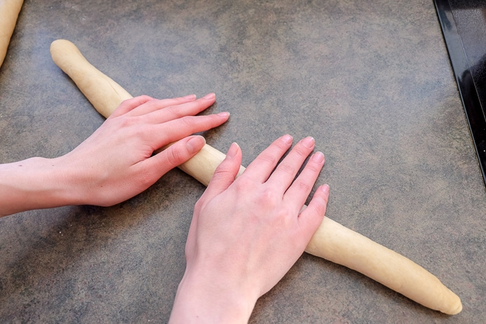 hands rolling sausage of sweet bread dough on counter top