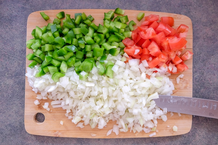 chopped onion pepper and tomato on wooden cutting board