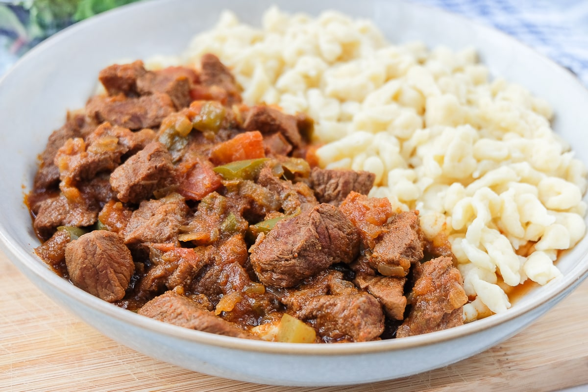 hungarian beef stew in bowl with nokedli noodles