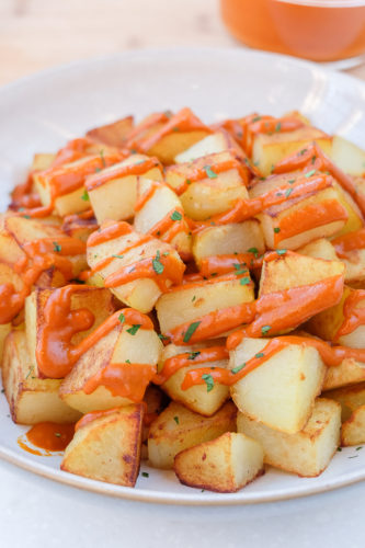 spanish fried potatoes with red bravas sauce in bowl