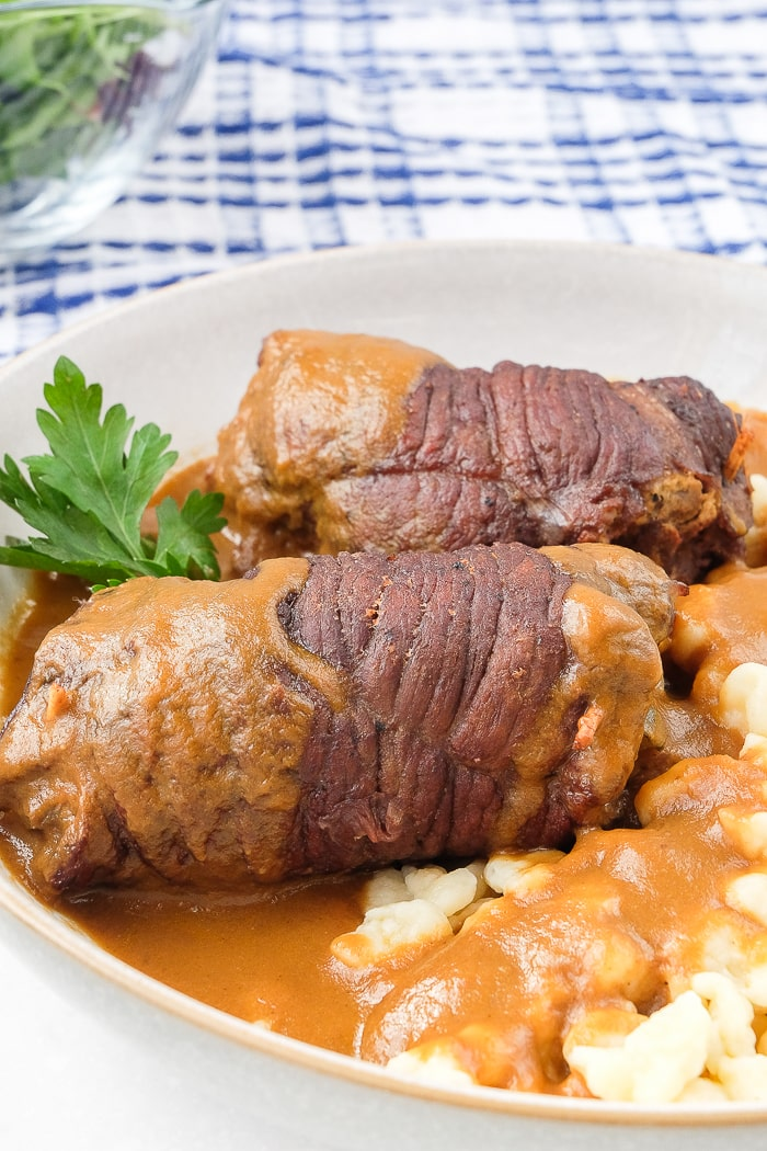 two beef rouladen in bowl with gravy and noodles