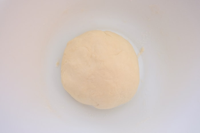 ball of pastry dough in white mixing bowl