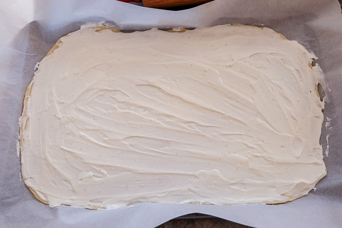 creamy white sauce spread out on flammkuchen dough on pan