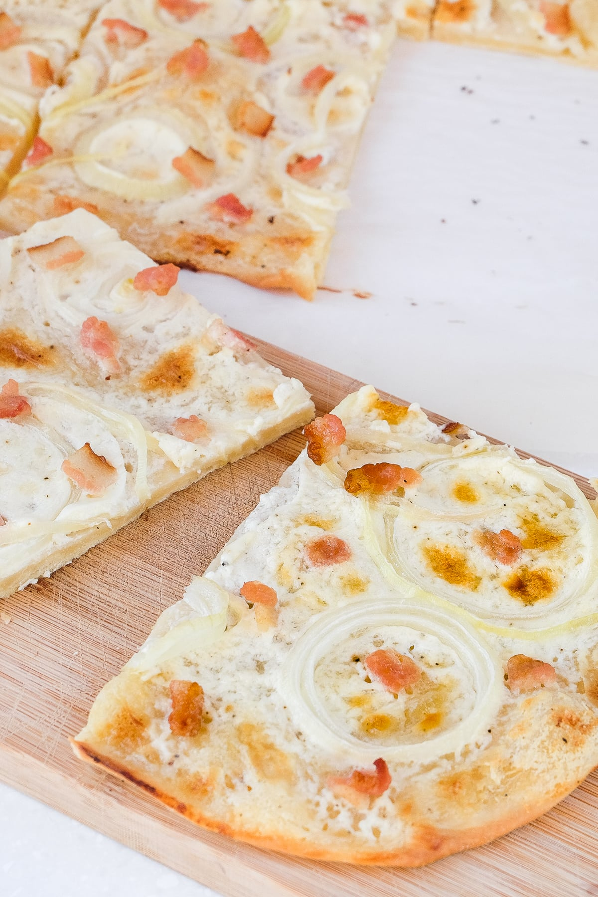 pieces of flammkuchen cut on wooden board