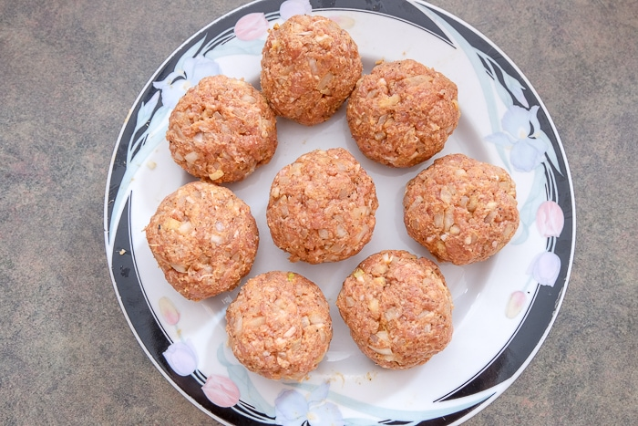 raw meatballs on plate on kitchen counter
