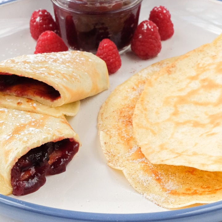 german pancakes on large plate with sugar and jam