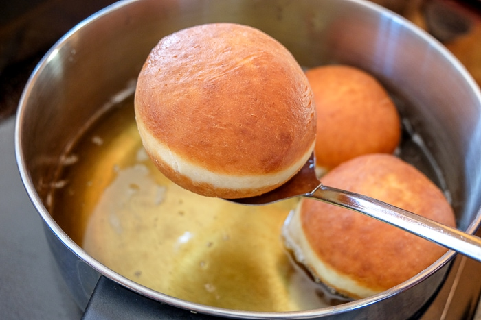 krapfen on straining spoon being lifted from silver pot of oil