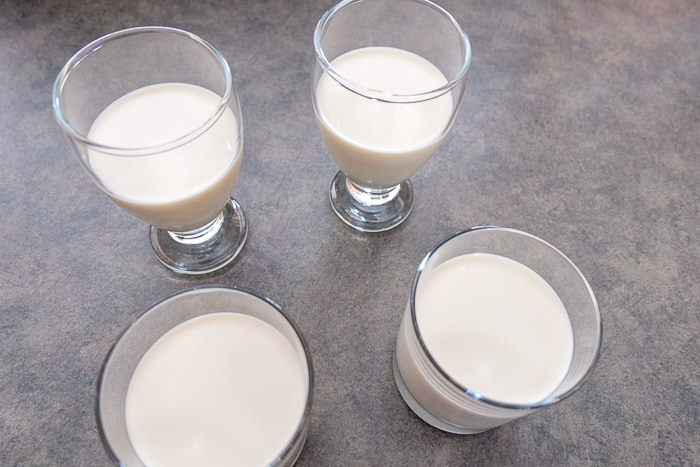four glasses on counter filled with panna cotta