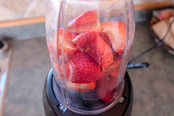strawberries in small blender on counter top