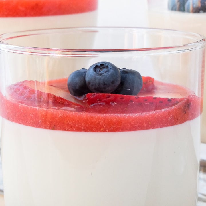 glass of panna cotta with berries and red puree on top