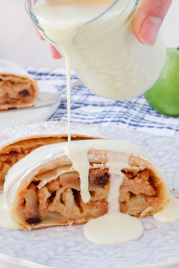 slice of apple strudel with vanilla sauce drizzling on top