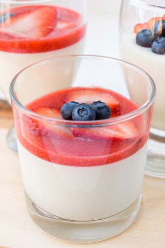 glass of panna cotta with berries and red berry puree on top