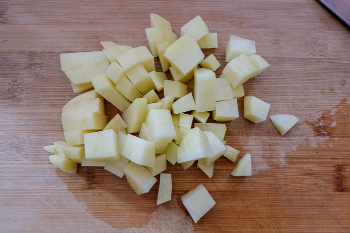 potatoes chopped up on wooden cutting board