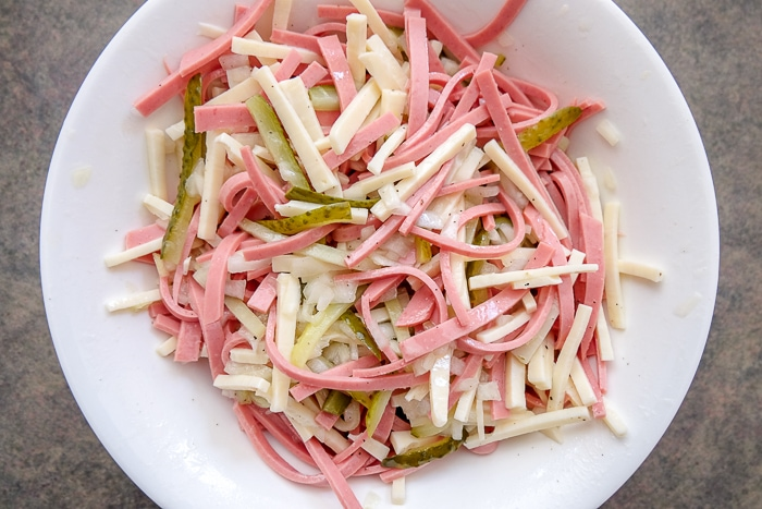 tossed wurstsalat in white bowl on counter