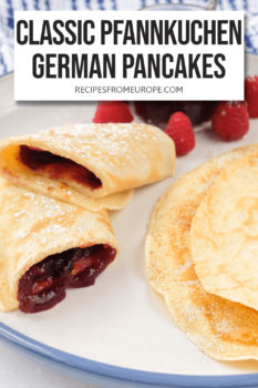 """rolled up pancake with jam in the middle and folded pancake with cinnamon sugar in the middle on plate with text overlay saying """"Classic Pfannkuchen German Pancakes"""""""