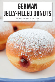 """deep-fried balls of dough with red jam in the middle and powdered sugar on top on plate with blue rim and text overlay saying """"German jelly-filled donuts"""""""