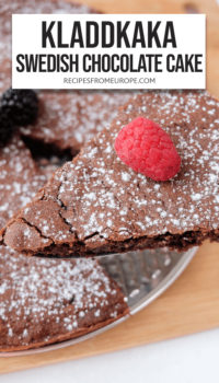 """Slice of chocolate cake with icing sugar and raspberry on top and rest of cake in background plus text overlay saying """"Kladdkaka Swedish chocolate cake"""""""