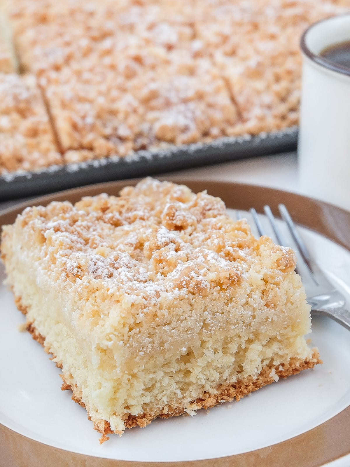 piece of coffee cake with streusel on plate with brown rim and cake in background