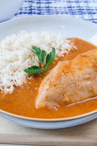 chicken paprikash with rice in bowl with blue towel behind