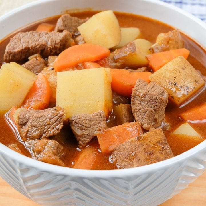 bowl of hungarian goulash on wooden plank with spoon beside