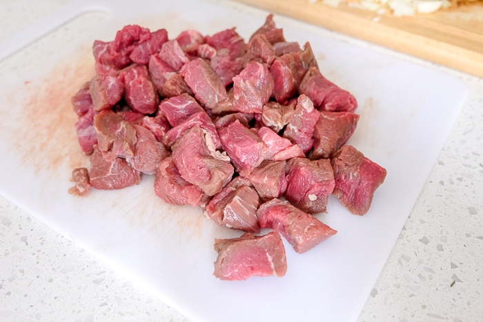 chopped pieces of raw beef on cutting board