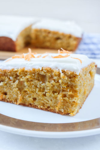 slice of carrot cake on plate with full cake behind